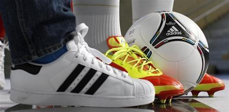 Different shoes and a soccer ball by German sporting goods maker are pictured before the company's annual news conference in the northern Bavarian town of Herzogenaurach March 7, 2012. REUTERS/Michaela Rehle