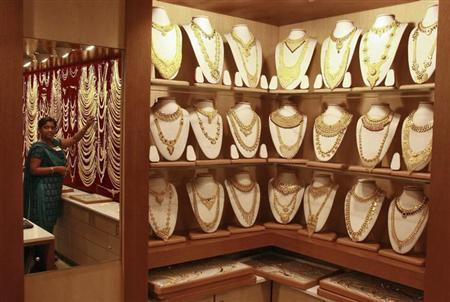 A salesgirl is reflected in a mirror inside a gold jewellery showroom in Kochi April 24, 2012. REUTERS/Sivaram V/Files