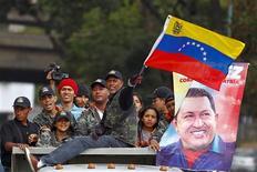 La prioridad del presidente venezolano Hugo Chávez es su salud y no la política, dijo el martes un alto cargo del partido de Gobierno, confirmando la visión de muchos analistas de que el retorno del mandatario a Caracas no acelerará su decisión de retomar el mando o hacerse a un lado. En la imagen, partidarios del presidente venezolano, Hugo Chávez, sobre un camión frente al hospital militar donde está ingresado Chávez, en Caracas, el 19 de febrero de 2013. REUTERS/Carlos Garcia Rawlins