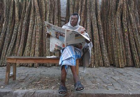 A trader reads a newspaper at a sugarcane wholesale market in Kolkata February 20, 2013. REUTERS/Rupak De Chowduhri