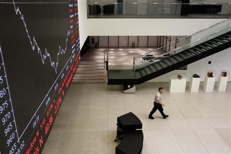 A man walks past an information bilboard showing the evolution of the FTSE 100 index at the Swiss exchange in Zurich, August 9, 2011. REUTERS/Christian Hartmann
