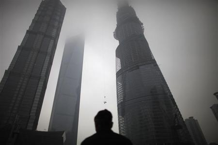 A man watches a construction crane lift a piece of steel at the Shanghai Tower (R) at the financial district of Pudong in Shanghai January 21, 2013. REUTERS/Carlos Barria