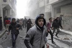 Free Syrian Army fighters and civilians react as they run after a jet missile hit the al-Myassar neighbourhood of Aleppo February 20, 2013. REUTERS/Hamid Khatib