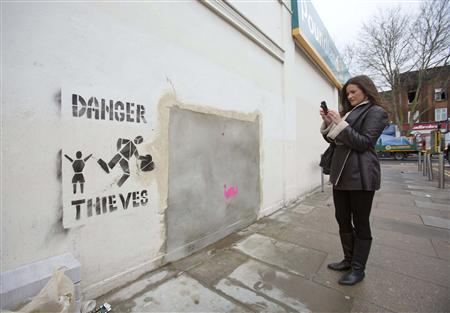 A woman takes a photograph of the former site of ''Banksy: Slave Labour'', a mural attributed to graffiti artist Banksy, in north London February 20, 2013. The mural is up for sale at a Miami auction house after the work, and a chunk of the North London wall it was spray-painted on, vanished late last week. REUTERS/Neil Hall