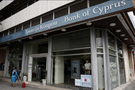 A cleaning worker holds a mop while working in front of a Bank of Cyprus branch in central Nicosia February 18, 2013. REUTERS/Yorgos Karahalis