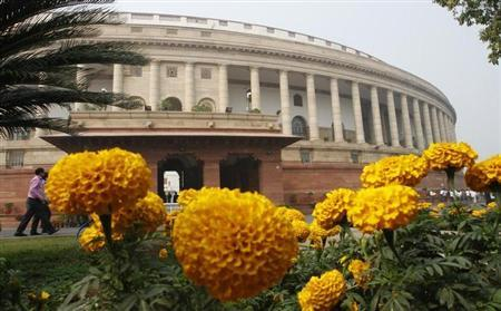 The Indian parliament building is pictured behind marigold flowers in New Delhi November 22, 2011. REUTERS/B Mathur/Files