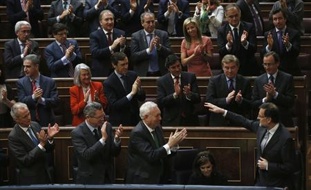 Spain's Prime Minister Mariano Rajoy (bottom R) is applauded by fellow People's Party (Partido Popular) deputies after his speech during the State of the Nation debate at Parliament in Madrid February 20, 2013. Rajoy on Wednesday said he would soon present a new series of fiscal reforms to boost job creation for young people and reduce the tax burden on small and medium-sized companies. REUTERS/Sergio Perez