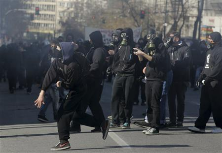 Masked protesters throw rocks at policemen following an anti-austerity march during a 24-hour strike in Athens February 20, 2013. Tens of thousands of Greeks took to the streets of Athens on Wednesday during a nationwide strike against wage cuts and high taxes that kept ferries stuck in ports, schools shut and hospitals with only emergency staff. REUTERS/Costas Baltas/ICON