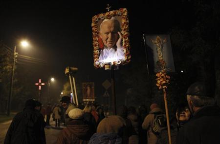 Catholic worshipers hold a decorated picture of the late pope John Paul II as they take part in a night pilgrimage of around 25 km (16 miles) from Blonie to Niepokalanow monastery which is held every month in Blonie, near Warsaw October 13, 2012. REUTERS/Kacper Pempel