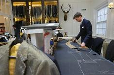 Cutter Finnan Lane cuts cloth for a suit at bespoke Savile Row tailors Anderson & Sheppard in central London February 14, 2013. Anderson & Sheppard had a 2012 turnover of 4 million pounds and growth has been over 13 percent every year since 2009. A number of other houses on Savile Row have also enjoyed over 10 percent growth in recent years with total revenue for the informal group of suitmakers now estimated to be 30-35 million pounds. Photograph taken February 14, 2013. REUTERS/Andrew Winning