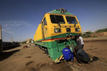 Workers prepare a train at Sudan Railway maintenance complex in Khartoum February 14, 2013. Sudan was once home to Africa's largest railway network, with more than 5,000 kilometres (3,100 miles) of track running from the Egyptian border to Darfur in the west, Port Sudan on the Red Sea coast and Wau in what is now South Sudan. Today, after decades of mismanagement and neglect, most of the country's rail track is out of service. But the government, with the help of Chinese money and expertise, wants to rebuild it and restore some of the industry's former glory. Picture taken February 14, 2013. To match Feature SUDAN-RAILWAY/ REUTERS/Mohamed Nureldin Abdallah