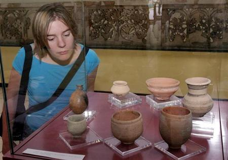 A woman examines a clay pots excavated from the ancient town of Ebla in central Syria at the Damascus museum, October 25, 2004. REUTERS/Khaled al-Hariri/Files