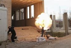 Un miembro del Ejército de Siria Libre corre para protegerse tras disparar un mortero contra el palacio presidencial en Damasco, feb 19 2013. Un misil cayó el miércoles sobre el centro de mando de la principal fuerza rebelde de Siria situado cerca de Damasco, hiriendo a su líder, reportaron activistas. REUTERS/ Mohammed Abdullah