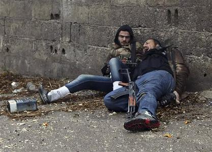 A Free Syrian Army fighter (L) looks at his comrade as he gets shot by sniper fire in the Ain Tarma neighbourhood of Damascus in this January 30, 2013 file photo. REUTERS/Goran Tomasevic/Files