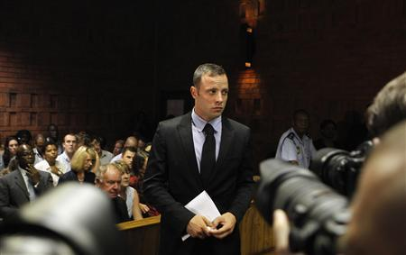 REFILE - CORRECTING TYPO Oscar Pistorius stands in the dock during a break in court proceedings at the Pretoria Magistrates court, February 20, 2013. ''Blade Runner'' Pistorius, a double amputee who became one of the biggest names in world athletics, was applying for bail after being charged in court with shooting dead his girlfriend, 30-year-old model Reeva Steenkamp, in his Pretoria house. REUTERS/Siphiwe Sibeko