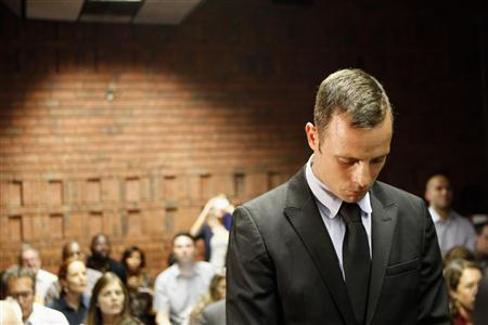 Oscar Pistorius stands in the dock during a break in court proceedings at the Pretoria Magistrates court, February 20, 2013. ''Blade Runner'' Pistorius, a double amputee who became one of the biggest names in world athletics, was applying for bail after being charged in court with shooting dead his girlfriend, 30-year-old model Reeva Steenkamp, in his Pretoria house. REUTERS/Siphiwe Sibeko