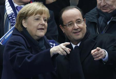 France's President Francois Hollande (R) points with German Chancellor Angela Merkel as they attend an international friendly soccer match between France and Germany at the Stade de France stadium in Saint-Denis, near Paris, February 6, 2013. REUTERS/Charles Platiau