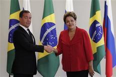 El primer ministro ruso, Dimitry Medvedev, se saluda con la presidenta de Brasil, Dilma Rousseff, en una reunión en el palacio del Gobierno en Brasilia, feb 20 2013. El primer ministro de Rusia, Dmitry Medvedev, se reunió el miércoles con la presidenta Dilma Rousseff durante una visita a Brasil que tiene como objetivo negociar la venta de equipo de defensa y tecnología nuclear a su socio del bloque BRICS de mercados emergentes. REUTERS/Ueslei Marcelino