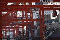 A container is loaded on a cargo ship at a port in Tokyo February 20, 2013. Japan's trade deficit widened to a record in January as energy imports jumped, highlighting a risk of trying to revive the country's export engine through policies that could weaken the currency without also pursuing broader economic reforms. REUTERS/Yuya Shino (JAPAN - Tags: BUSINESS MARITIME)