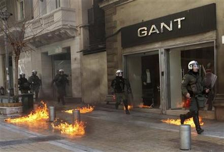Riot police run by closed shops after protesters threw a petrol bomb following an anti-austerity march during a 24-hour strike February 20, 2013. Tens of thousands of Greeks took to the streets of Athens on Wednesday during a nationwide strike against wage cuts and high taxes that kept ferries stuck in ports, schools shut and hospitals with only emergency staff. REUTERS/Giorgos Moutafis