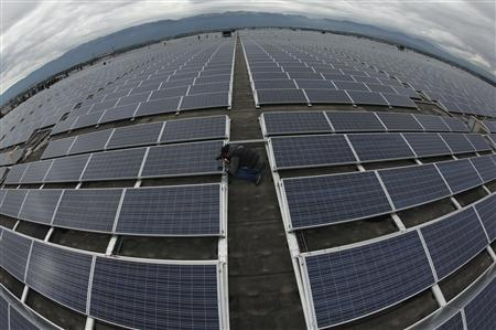 A photographer takes a picture of solar panels on the roof of the Palexpo Exhibition Center in Geneva October 16, 2012. REUTERS/Denis Balibouse