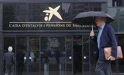 Caixabank se encuentra preparando una importante reducción de plantilla para reducir la estructura de costes de la entidad bancaria con la mayor red de sucursales del país, dijeron el miércoles fuentes sindicales y de la entidad. En la imagen de archivo, un hombre camina junto a la entrada principal de Caixabank en Barcelona, el 26 de octubre de 2012. REUTERS/Albert Gea
