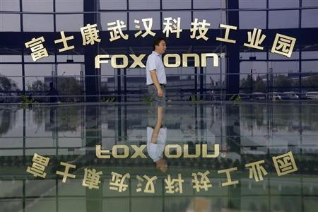 A man walks past a logo of a Foxconn factory in Wuhan, Hubei province, August 31, 2012. REUTERS/Stringer