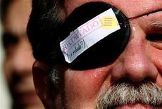 """Miles de jueces y fiscales españoles estaban llamados a la huelga el miércoles en protesta por las diversas reformas judiciales emprendidas por el Gobierno. En la imagen, un hombre con un parche que dice """"Recortado o robado?"""" en una huelga de empleados españoles de Justicia contra las medidas de austeridad del Gobierno, en Barcelona, el 20 de febrero de 2013. REUTERS/Gustau Nacarino"""