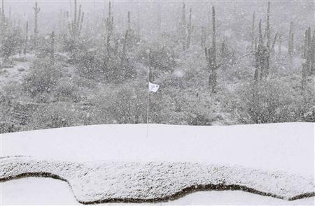 The 18th green is covered in snow as play was suspended during the first round of the WGC-Accenture Match Play Championship golf tournament in Marana, Arizona February 20, 2013. REUTERS/Matt Sullivan