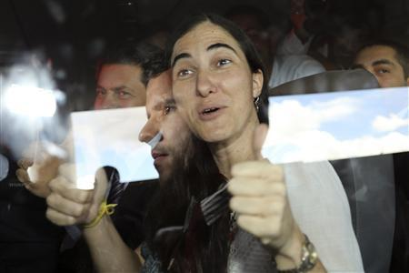 Cuba's best-known dissident, blogger Yoani Sanchez, gestures from the window of a bus as she arrives for a visit to Brazil's Congress in Brasilia February 20, 2013. REUTERS/Fabio Rodrigues-Pozzebom