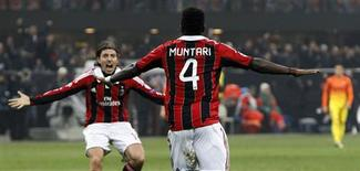 Sulley Muntari félicité par son coéquipier du Milan AC Riccardo Montolivo après avoir marqué le deuxième but de la rencontre. Le club lombard a battu Barcelone 2-0 à domicile mercredi en huitièmes de finale aller de la Ligue des champions. /Photo prise le 20 février 2013/REUTERS/Alessandro Garofalo