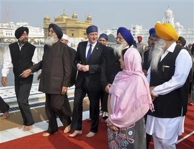 Britain's Prime Minister David Cameron (3rd L) walks inside the premises of the holy Sikh shrine of Golden temple in the northern Indian city of Amritsar February 20, 2013. Cameron on Wednesday became the first serving prime minister to voice regret about one of the British Empire's bloodiest episodes in India, the Jallianwala Bagh massacre, and laid a wreath at Amritsar, scene of a notorious massacre of unarmed civilians. REUTERS/Munish Sharma