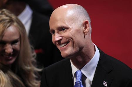 Florida Governor Rick Scott greets an attendee in the audience before the start of the final U.S. presidential debate in Boca Raton, Florida October 22, 2012. REUTERS/Joe Skipper