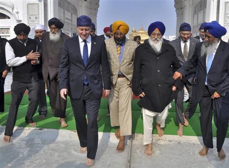 Britain's Prime Minister David Cameron (4th R) walks inside the premises of the holy Sikh shrine of Golden temple in Amritsar February 20, 2013. REUTERS/Stringer