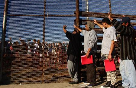 A group of recently deported immigrants stand near the double steel fence that separates San Diego and Tijuana at the border in Tijuana December 10, 2011. REUTERS/Jorge Duenes