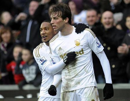 Swansea City's Michu (R) celebrates with teammate Jonathan de Guzman after scoring a goal against Queens Park Rangers during their Premier League match at the Liberty Stadium in Swansea, February 9, 2013. REUTERS/Rebecca Naden