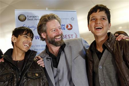 Director Sam French (C) and 14-year-old Afghan actors Fawad Mohammadi (L) and Jawanmard Paiz of the Oscar nominated live-action short film Buzkashi Boys, laugh together after arriving at Los Angeles International Airport (LAX) in Los Angeles, California February 20, 2013. REUTERS/Patrick Fallon