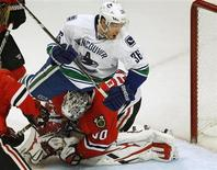 Vancouver Canucks' Jannik Hansen (top) crashes into Chicago Blackhawks' goalie Ray Emery during the third period of their NHL hockey game in Chicago, Illinois, February 19, 2013. REUTERS/Jim Young