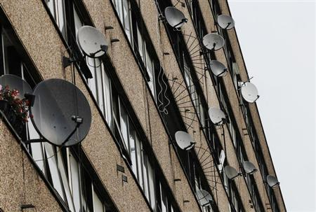 Satellite dishes are seen on the side of a block of flats in south London July 29, 2011. REUTERS/Luke MacGregor
