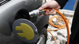 Сотрудник BMW демонстриует способ заправки электромобиля на презентации в Берлине, 18 февраля 2009 года. Эстония стала первой в мире страной, покрывшей всю свою территорию сетью заправок для автомобилей, оснащенных электродвигателями. REUTERS/Fabrizio Bensch (GERMANY)