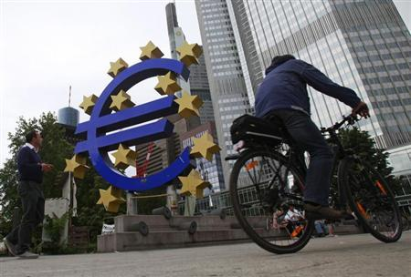 A man cycles past the euro sign at the European Central Bank (ECB) headquarters in Frankfurt July 11, 2012. REUTERS/Alex Domanski