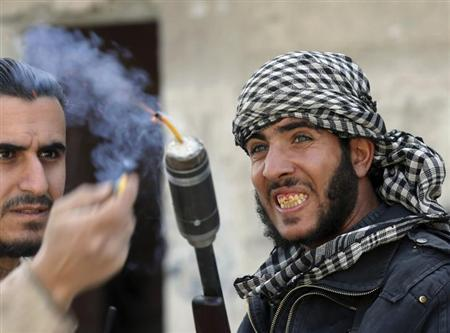Fighters from the Free Syrian Army's Tahrir al Sham brigade use a shotgun to fire a fuse-lit stick of dynamite at Syrian Army soldiers in the Arabeen neigbourhood of Damascus in this February 9, 2013 file photo. REUTERS/Goran Tomasevic/Files
