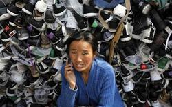 Продавщица обуви разговаривает по телефону в индийском городе Шринагар 28 марта 2012 года. Российский конгломерат АФК Система, лишившийся большинства лицензий на оказание услуг связи в Индии, намерен участвовать в новом аукционе на радиочастоты, но прекратит операции в 10 из 22 округов, сообщила компания в четверг. REUTERS/Fayaz Kabli
