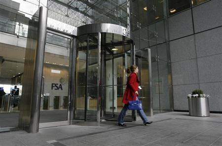 A woman leaves the offices of the Financial Services Authority (FSA) in Canary Wharf, London in this November 19, 2010 file photograph. REUTERS/Simon Newman/Files