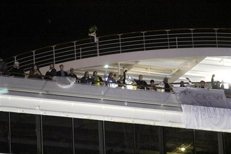 Passengers wait to leave the Carnival Triumph cruise ship after reaching the port of Mobile, Alabama, February 14, 2013. REUTERS/ Lyle Ratliff