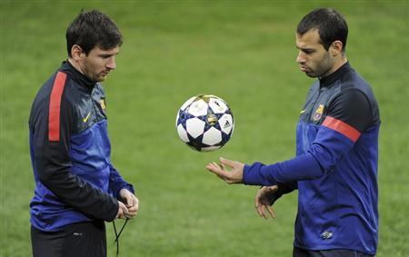 Barcelona's Lionel Messi (L) and Javier Mascherano talk during a training session at the San Siro Stadium in Milan February 19, 2013. REUTERS/Stringer