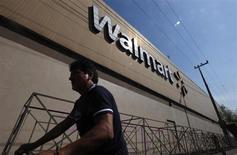 Мужчина у магазина Wal-Mart в Мехико 11 января 2013 года. Wal-Mart Stores Inc нарастил квартальную прибыль благодаря налоговым ставкам, которые оказались ниже, чем ожидалось, за счет чего удалось компенсировать слабые продажи в США. REUTERS/Edgard Garrido