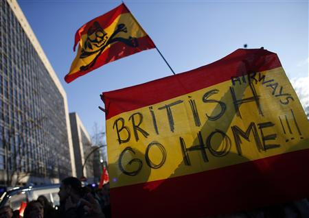 Iberia airline workers hold up a sign with the colours of the Spanish flag during a protest outside Iberia headquarters on the third day of a week-long strike February 20, 2013. REUTERS/Paul Hanna