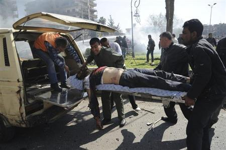 Men try to help a man who is injured after an explosion at central Damascus February 21, 2013, in this handout photograph released by Syria's national news agency SANA. REUTERS/Sana
