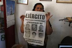 María Orozco, madre de un desaparecido, muestra un afiche en Iguala, México, feb 20 2013. Decenas de personas fueron secuestradas y asesinadas en México por las fuerzas de seguridad en los últimos años durante la ofensiva contra el narcotráfico del ex presidente Felipe Calderón, dijo el organismo Human Rights Watch, en un reporte divulgado el miércoles. REUTERS/Tomas Bravo